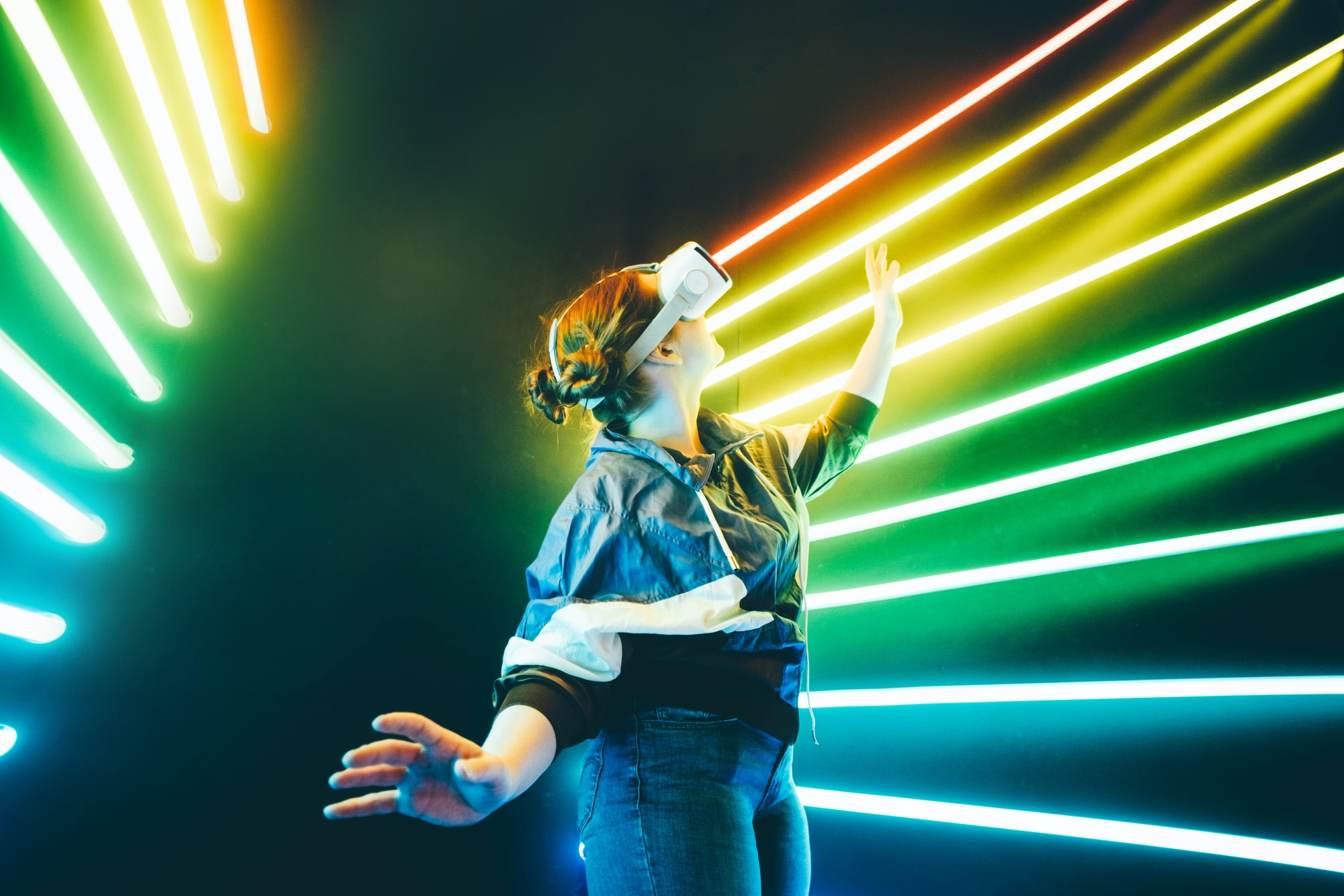 Girl using VR goggles in colorful neon lights